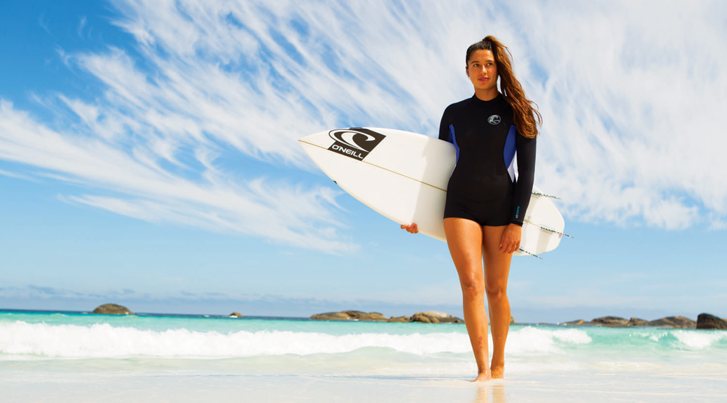 lady surfer in summer wetsuit walking on the beach