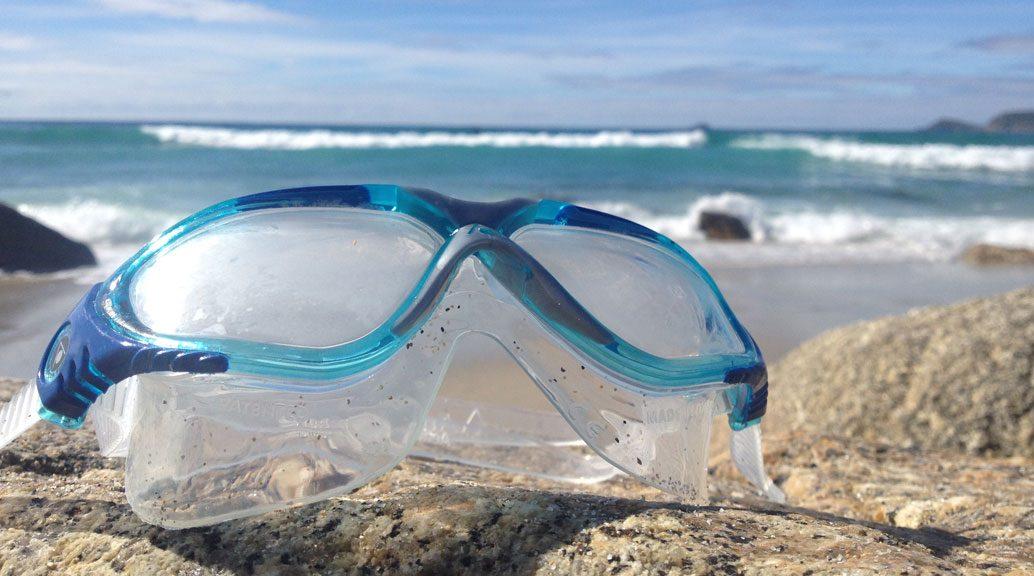 aqua sphere swim goggles on beach
